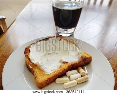 Toast with cream cheese, cold brew black coffee and vitamins for breakfast.