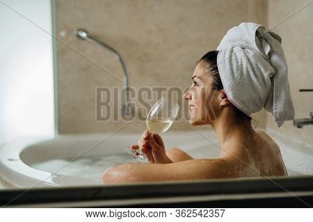 Woman Relaxing At Home In The Hot Tub Bath Ritual,drinking Wine.relaxing Spa Night In Bathroom.good