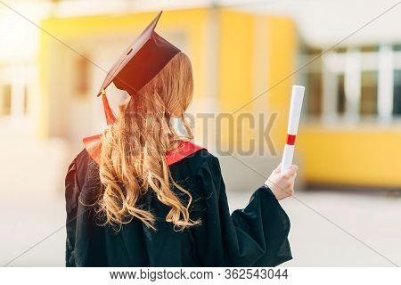 Graduation Day, Back View, Student In A Graduation Cap And Dress With A Diploma. The Concept Of Succ