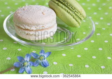 White And Pistachio Macaroons On A Transparent Saucer And Blue Spring Flowers On A Light Green Napki