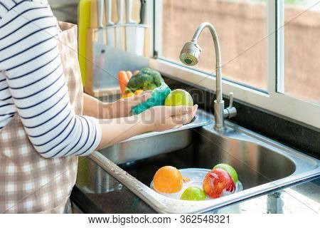 Asian Healthy Woman Washing An Apple And Other Fruit Above Kitchen Sink And Applying A Fruit / Veget
