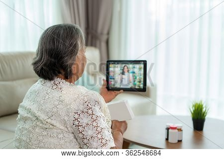 Asian Senior Woman Using Video Conference, Make Online Consultation With Pharmacy Consulting About I