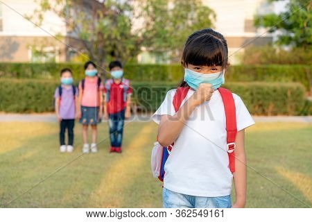 Asian Girl Preschool Child Student Wearing Healthy Face Mask Sneeze With Friends In Background. Who