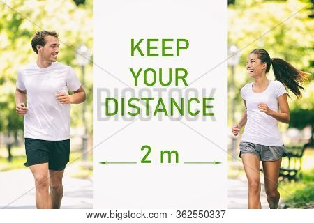 KEEP YOUR DISTANCE Covid-19 two meters warning for social distancing prevention text message sign. People walking in park street talking during walk run jog. Asian woman jogger running with man.
