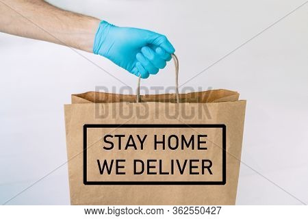Home delivery food grocery delivered with gloves for COVID-19 quarantine from coronavirus social distancing. text message written : STAY HOME, WE DELIVER man giving bag as Corona virus prevention.