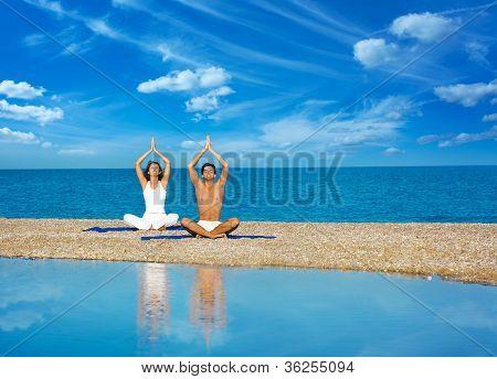Couple on the Beach Practicing Yoga