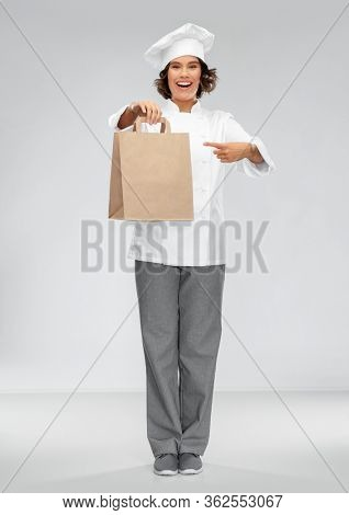 cooking, delivery and people concept - happy smiling female chef in toque with takeaway food in paper bag over grey background