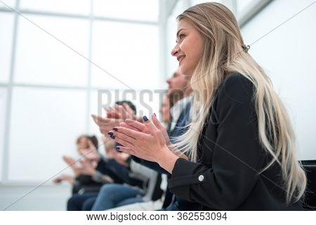 young woman and her colleagues applaud together.