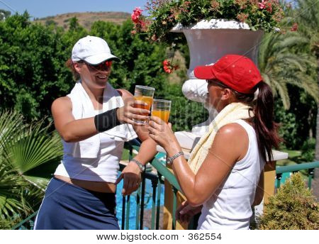 Two Young, Attractive, Fit And Healthy Women Drinking Juice After A Hot Game Of Tennis