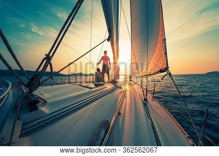 Young couple sailing on the boat at sunset