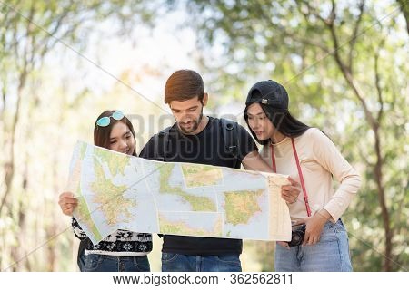 Multi Ethnic Travelers Looking At The Map On Travel Vacations With Nature Background. Diversity, Fri
