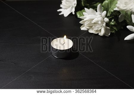 Funeral Symbol. A Burning Candle On A Black Background, A Bouquet Of White Flowers In The Background