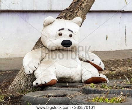 A Sad Plush Toy Of A White Dirty Big Teddy Bear, Lost And Forgotten. Bear Alone On The Ground