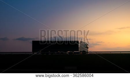 Silhouette Of A Truck On Road At Sunset.semi Truck Trailer Silhouette With Setting Sun.delivery Truc