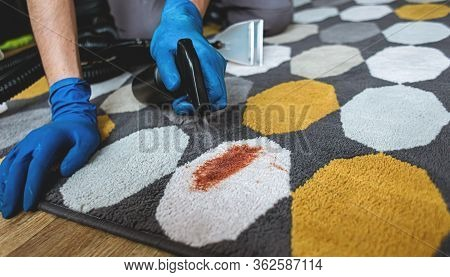 Close-up Of Persons Hand Cleaning Stain On Carpet With Sponge.