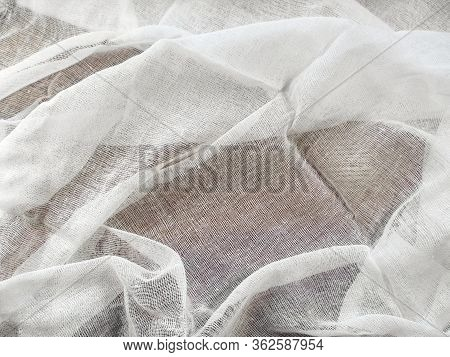 Texture Of White Medical Gauze On A Dark Surface. The Mesh Fabric Lies Carelessly With Pleats, Blank