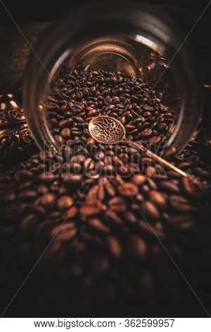 Coffee Beans Spilled Out Of A Glass Jar, Dark Background