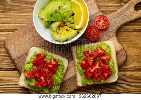 Homemade Healthy Toasts With Smashed Avocado And Chopped Fresh Tomatoes On Cutting Board On Wooden R