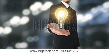 Hand Of Holding Illuminated Light Bulb. Innovation Inspiration Concept.
