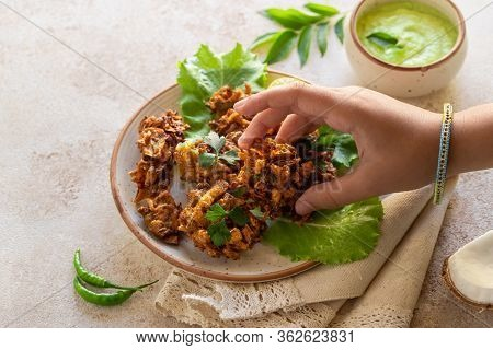 Indian Cuisine Indian Food. Pakora With Coconut Chutney Sauce Curry Leaves. Hand Of Young Indian Wom