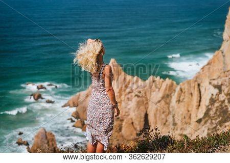 Beautiful Blond Women Enjoying Ocean Breeze On Coastline Of Praia Da Ursa Beach In Morning Light. Su