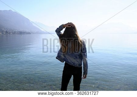 Young Girl With Jean Jacket Standing In Front Of Annecy Lake, Savoy, France
