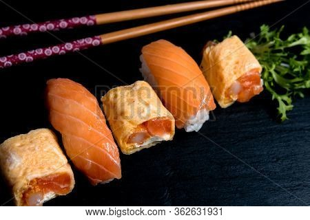 Japanese Cuisines Nigiri Sushi Set On Black Plate Served With Wasabi, Soy Sauce. Sushi Roll With Sal