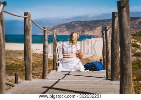 Adult Female Tourist Sitting On Path Leading To Praia Do Guincho Beach. Cascais, Portugal. This Is P
