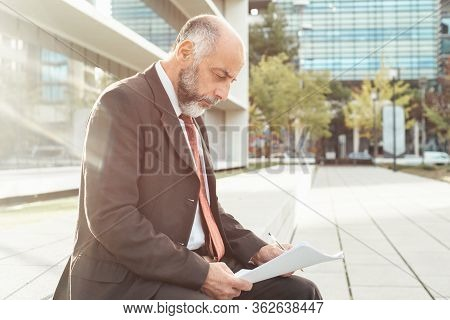 Side View Of Concentrated Businessman Working With Reports. Focused Bearded Mature Man Sitting On St