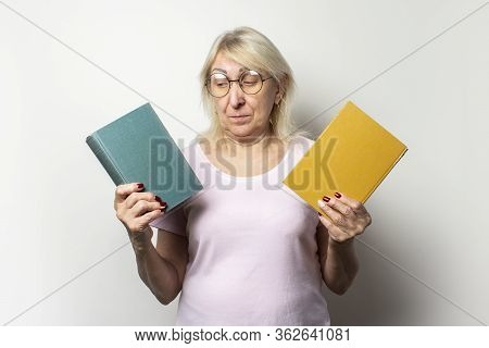 Portrait Of An Old Friendly Woman With A Smile In A Casual T-shirt And Glasses Holds Two Books On An