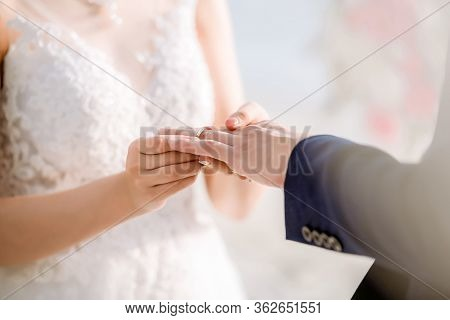 Wedding Rings.she Put The Wedding Ring On Him.close Up Bride Put The Ring On Groom. Wedding Ceremony