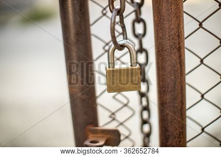 Lock On A Chain Link Security Fence. Chicken Wire Fence Gate Is Locked With A Chain And A Padlock. P