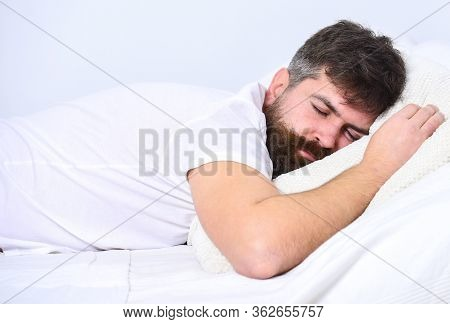 Man In Shirt Laying On Bed, White Wall On Background. Guy On Calm Face Sleeping On White Sheets And