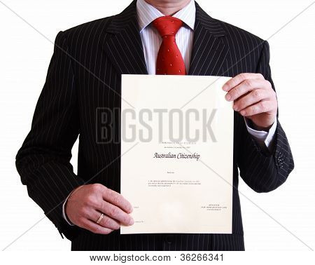 Man in black suit holding Australian Citizenship Certificate