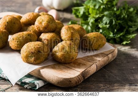 Traditional Cod Fritters With Garlic And Parsley On Wooden Table
