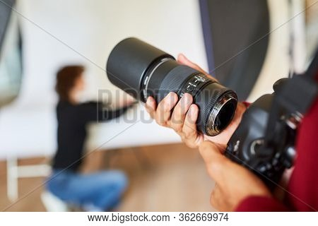 Photographer with reflex camera and lens in the photo studio