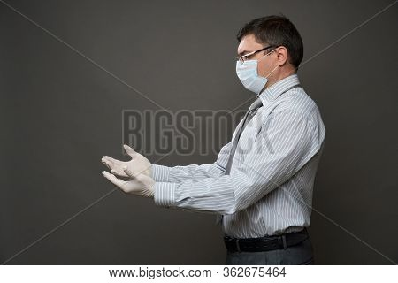 a man dressed as a businessman looking on his palms, posing in studio on gray background, medical face mask and protective gloves, shirt and tie - concept of quarantine and antivirus protection