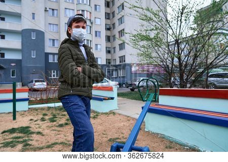teen boy stands by seesaw on playground near high-rise buildings with apartments, a medical mask on his face protects against viruses and dust