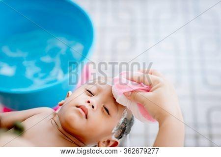 Bath Time For A Cute Little Newborn Baby. Newborn Baby Boy Take A Bath. Mom Cleaning Her Baby Hair W