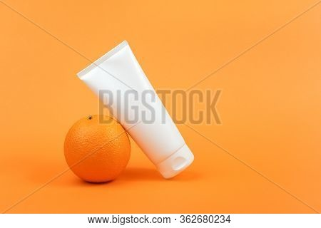 White Blank Cosmetic Bottle, Tube Of Cream, Lotion For Body, Face Or Hand, Orange Fruit. Concept Cos