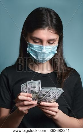 Woman In Face Mask Get Allowance During Coronavirus Covid 19. Girl Is Holding Dollar Banknotes. Mone
