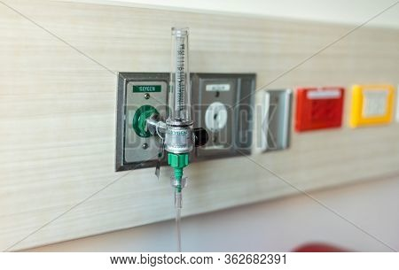 Oxygen Flow Meter Plugged In The Green Outlet On Hospital Wall, Medical Equipment. Oxygen For Patien