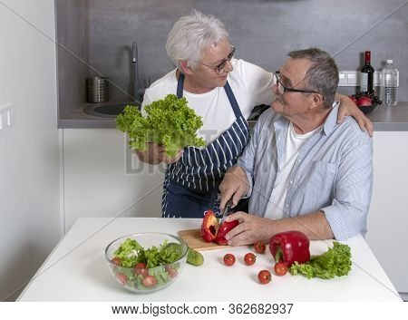 Senior Couple Preparing Fresh Green Salad Together. Healthy Food During Coronavirus Quarantine. Mode