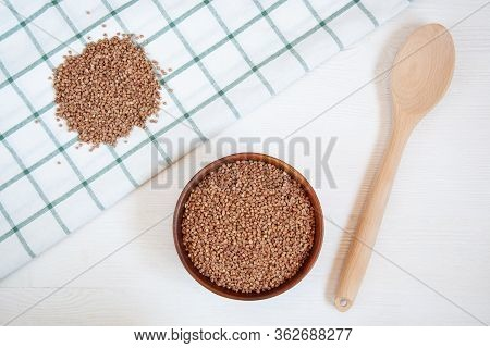 Buckwheat Groats In A Wooden Bowl On A White Table And Scattered Buckwheat Groats Nearby.