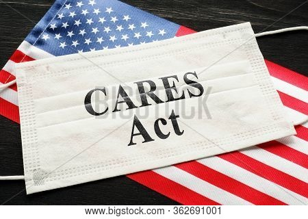 American Flag And Mask With Sign Cares Act. Coronavirus Aid, Relief, And Economic Security Law Conce