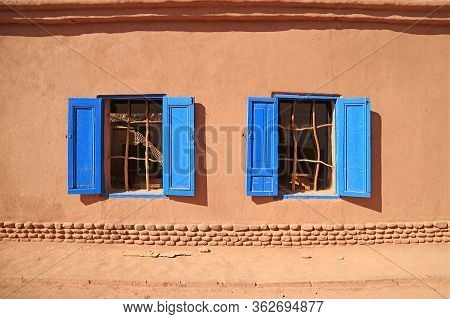 Vivid Blue Colored Windows On Brown Adobe Facade In The Sunlight, Northern Chile