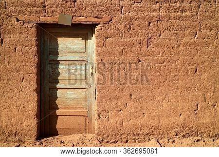 Old Wooden Door On Adobe Brick Facade In The Sunlight, A Small Town In Northern Chile