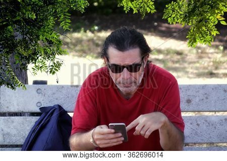 Outdoor portrait of a mid adult man sitting on park bench using mobil phone in Florida, USA