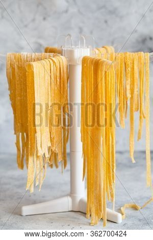 Homemade Italian Tagliatelle Hanging On A Pasta Drying Rack. Fresh Noodle Drying On Drying Rack.  Se