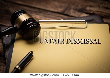 Unfair Dismissal Text On Document And Gavel Isolated On Wooden Office Desk Close Up